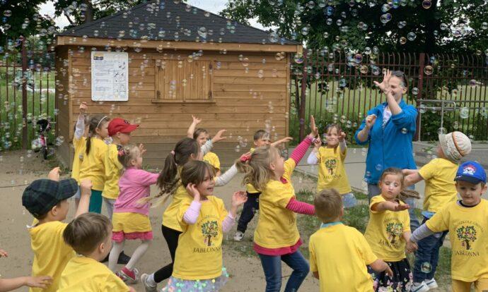Nauczycielka bawi się z dziećmi wśród baniek mydlanych.